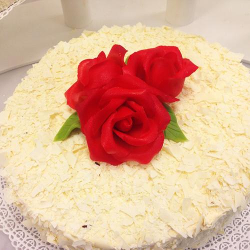 Hochzeitstorte mit weißen Schokoraspeln und Rosen
